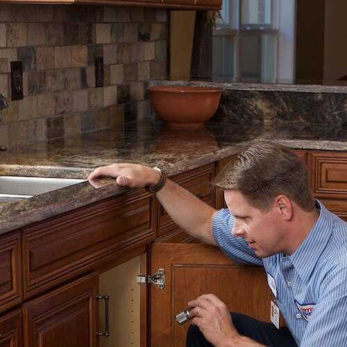 technician checking drain and faucet