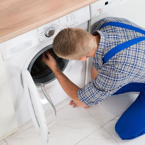 High Angle View Of Male Worker In Overall Making Washer